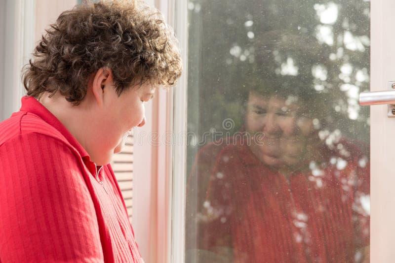 Умственно - неработающая женщина смотря к ее отражению на окне стоковая фотография