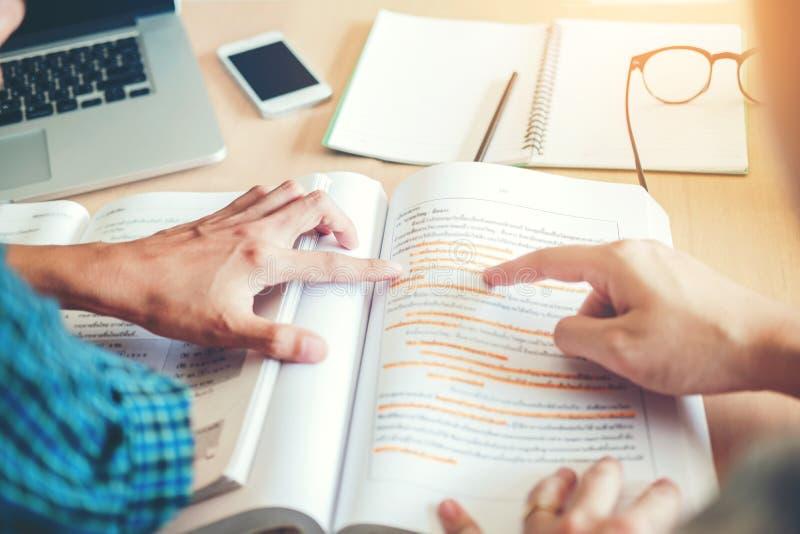 Университет изучая друзей изучая и читая книги в clas стоковая фотография