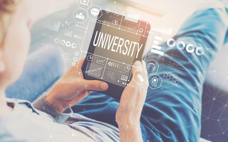 Университет с человеком используя планшет стоковая фотография