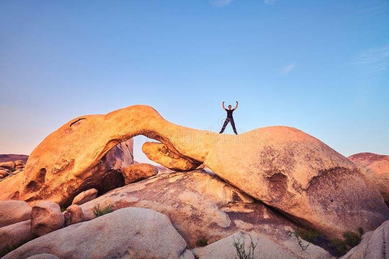 Уникально горные породы с женским альпинистом на заходе солнца стоковая фотография rf