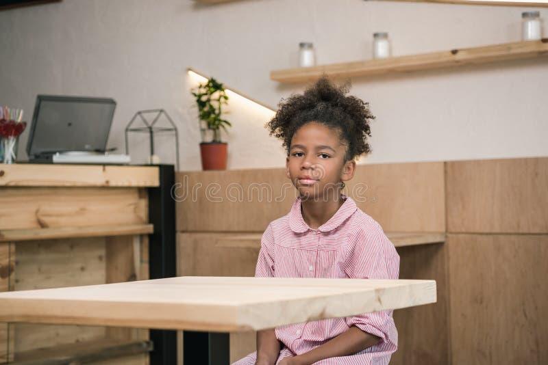 унылая Афро-американская девушка сидя самостоятельно стоковая фотография rf
