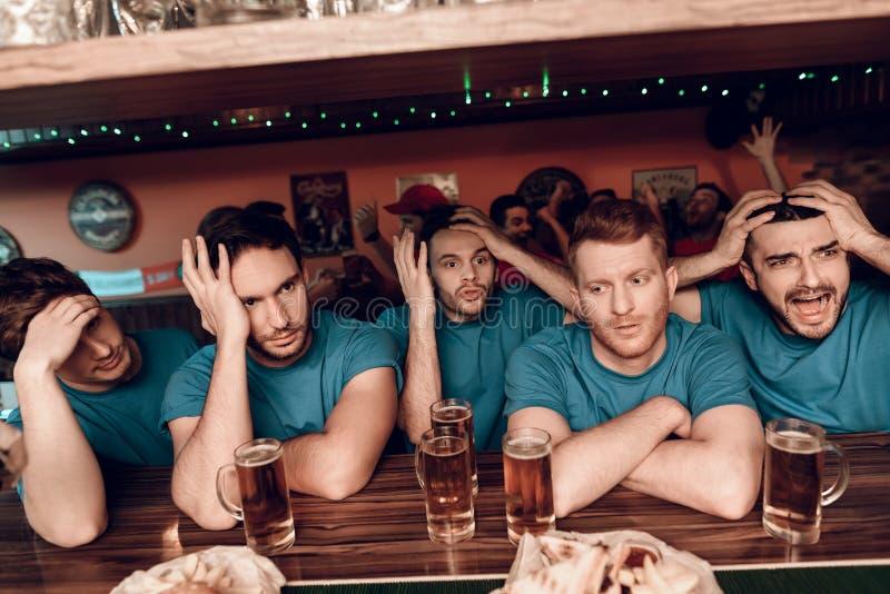 Унылая голубая команда дует на баре в баре спорт при красные вентиляторы команды веселя в предпосылке стоковое фото