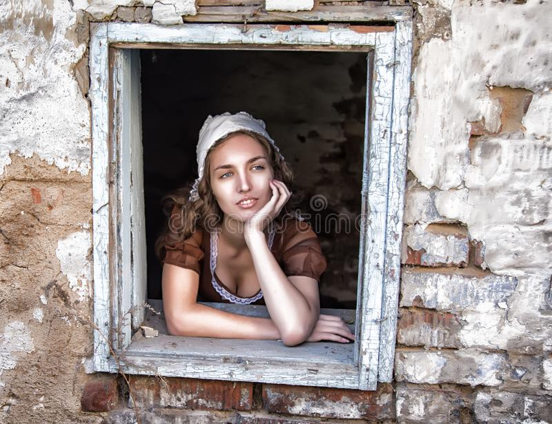 Унылая женщина в деревенском платье сидя около окна в старом чувстве дома сиротливом Стиль Золушкы стоковые фото