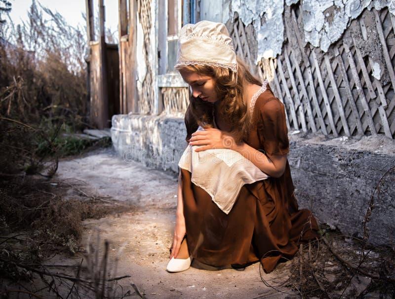 Унылая женщина в деревенском платье сидя около старой кирпичной стены в старом доме и пробуя одеть белый ботинок Стиль Золушкы стоковое фото