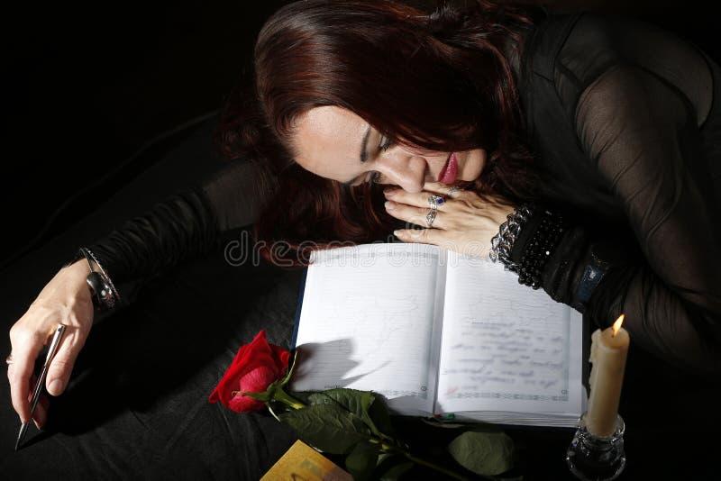 Унылая женщина лежит на таблице Несчастная влюбленность Страдать о влюбленности стоковое фото rf