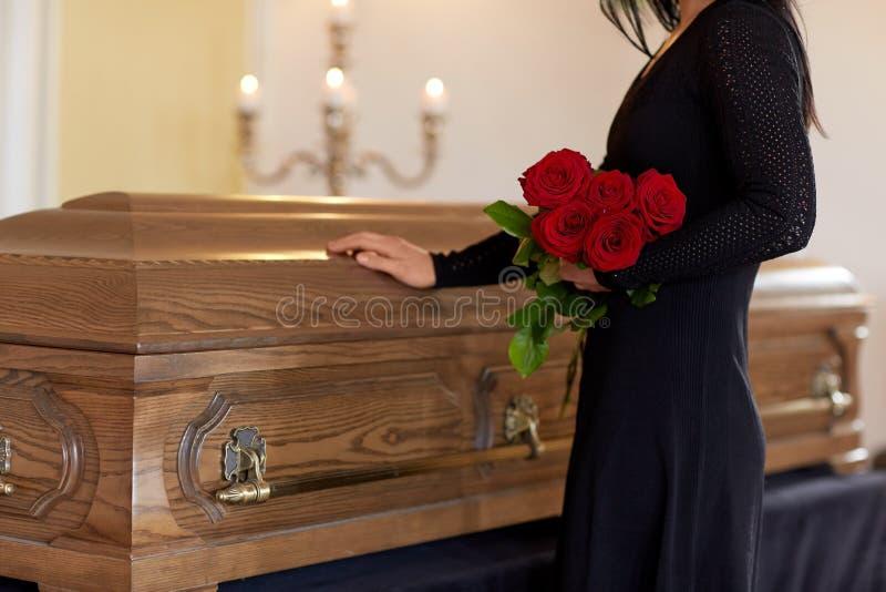 Унылая женщина с красными розами и гробом на похоронах стоковое изображение rf