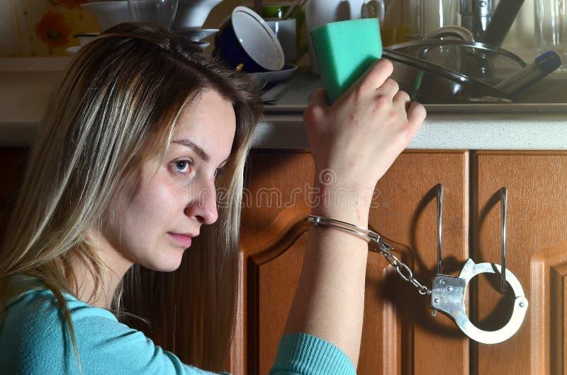 Унылая и утомленная девушка надеванная наручники к счетчику кухни с много стоковые изображения rf