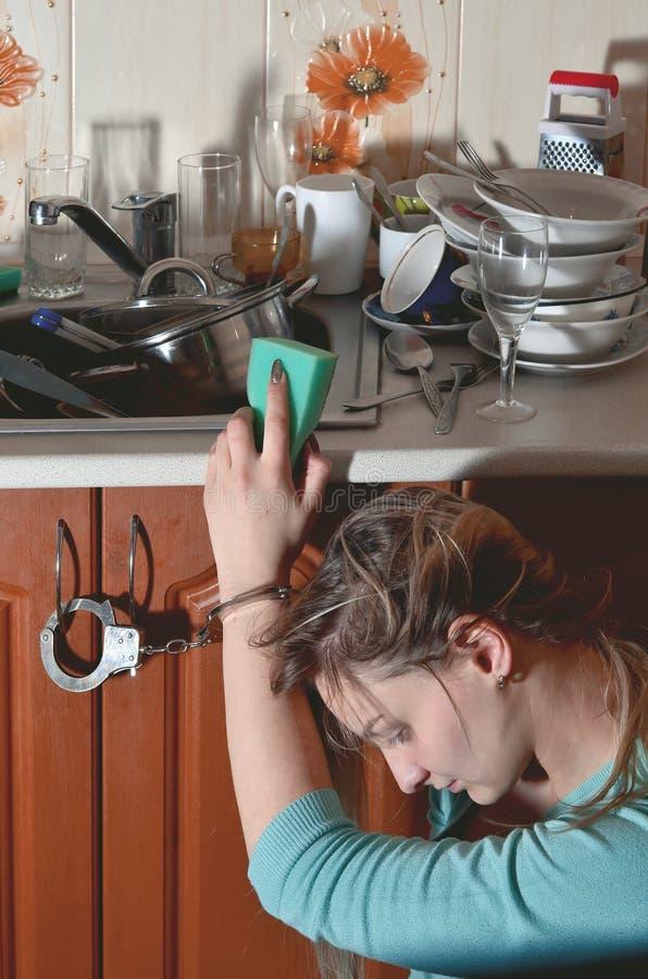 Унылая и утомленная девушка надеванная наручники к счетчику кухни с много стоковая фотография rf