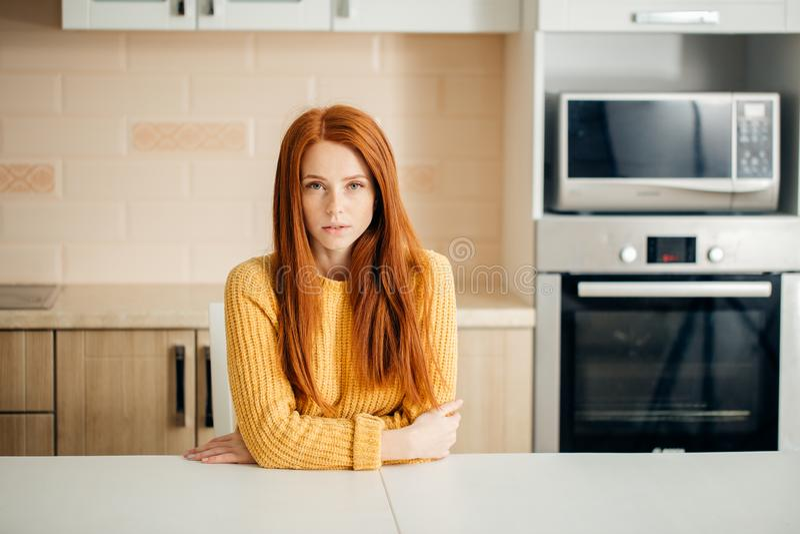 Унылая молодая женщина сидя в кухне дома стоковые фотографии rf