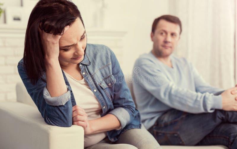 Унылая несчастная женщина держа ее лоб стоковая фотография