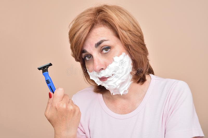 Унылая середина постарела женщина с брить пену на ее стороне держа и показывая бритву стоковые фото