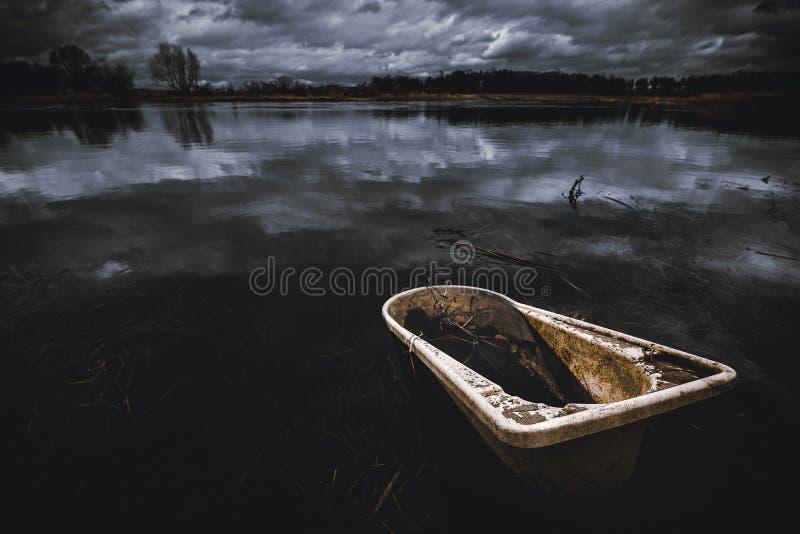 Унылое изображение старой ванны брошенное прочь в речную воду Темное пасмурное выравниваясь время стоковое фото rf