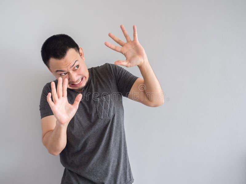 Унылый и вспугнутый азиатский человек в черной футболке стоковое фото rf