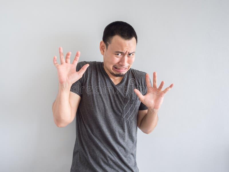 Унылый и вспугнутый азиатский человек в черной футболке стоковое изображение rf