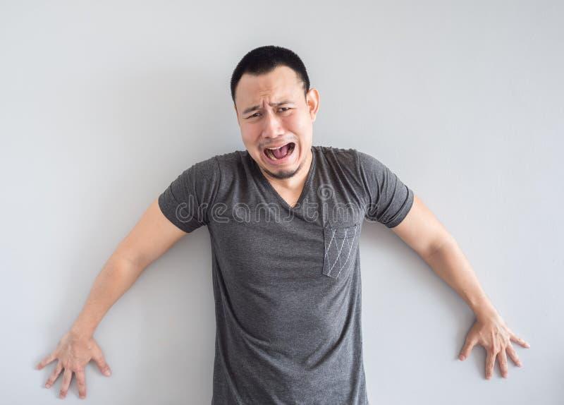 Унылый и вспугнутый азиатский человек в черной футболке стоковое фото