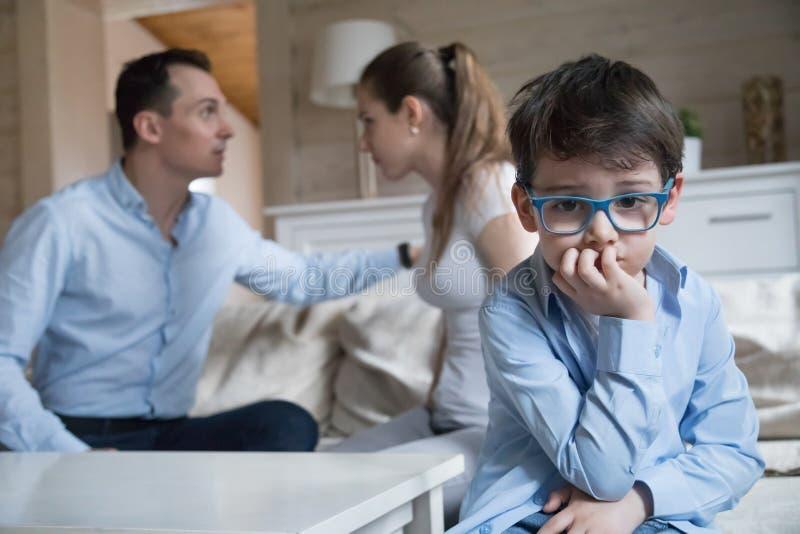 Унылый малый мальчик страдает от родителей воюет и враждует стоковые фотографии rf