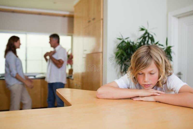 Унылый мальчик должен слушать к родителям бой стоковая фотография rf