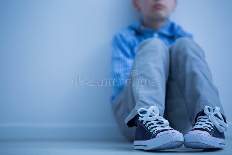 Унылый мальчик сидит самостоятельно стоковые фотографии rf