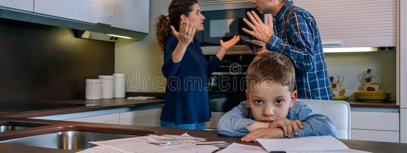 Унылый мальчик смотря камеру пока его родители спорят стоковые изображения rf