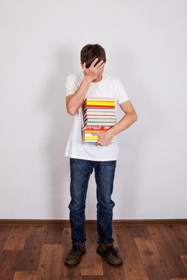 Унылый молодой человек с книги стоковая фотография
