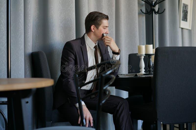 Унылый человек в деловом костюме сидя с телефоном в кафе он осадка ` s стоковые фотографии rf