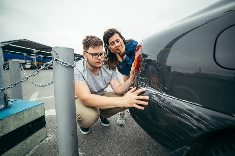 Унылый человек смотря на царапине автомобиля, стойке женщины за им стоковое изображение