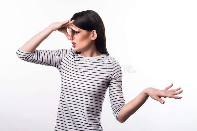 Унылая девушка закрывая ее нос стоковые изображения
