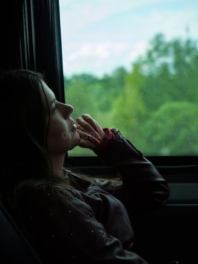 Унылая девушка смотрит вне окно автомобиля на дождливый день стоковая фотография rf