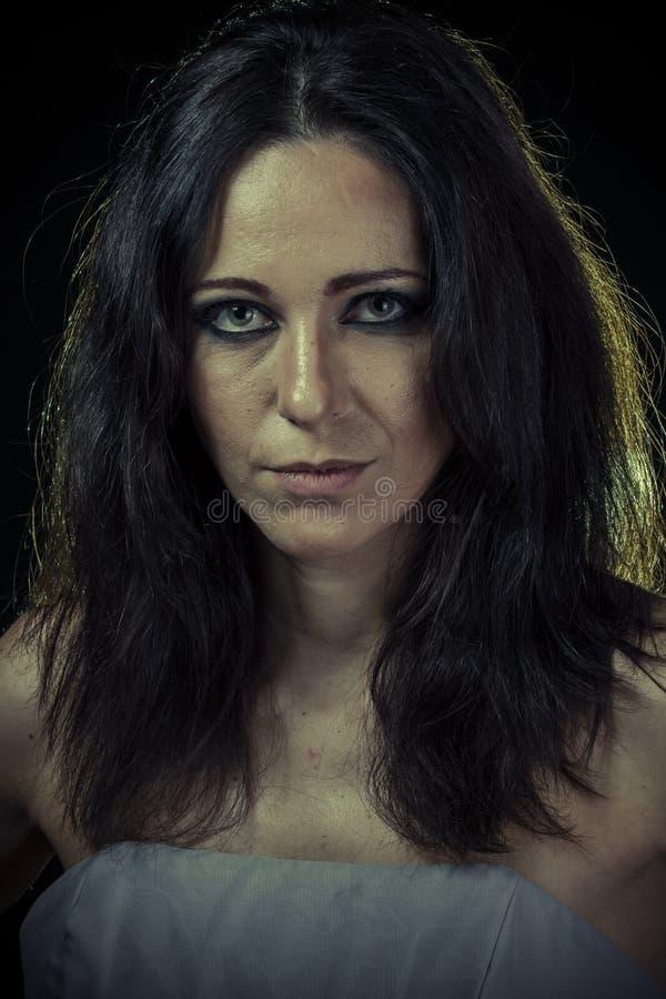 Унылая женщина брюнет с длинными волосами и мантией вечера стоковое изображение rf