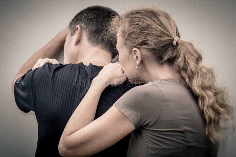 Унылая женщина обнимая ее супруга стоковая фотография rf