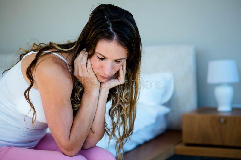 унылая женщина сидя на ее спальне стоковое изображение rf