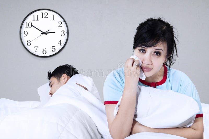 Унылая женщина сидя на кровати стоковые изображения rf