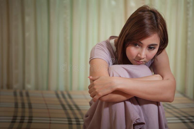 Унылая женщина сидя на кровати стоковое фото rf