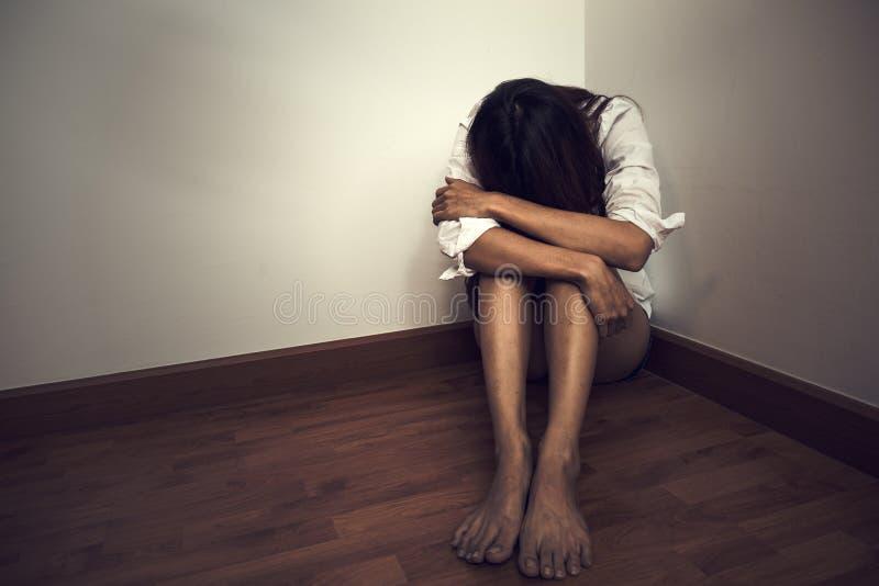 Унылая женщина сидя самостоятельно в пустой комнате стоковые фото