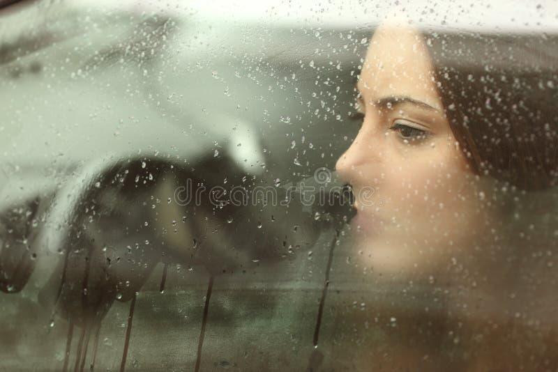 Унылая женщина смотря через окно автомобиля стоковые фотографии rf