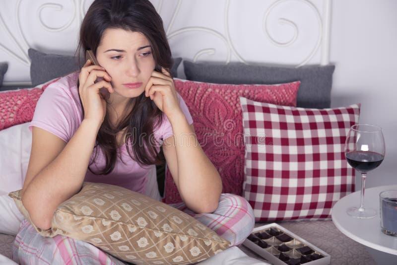 Унылая женщина с телефоном стоковое фото rf
