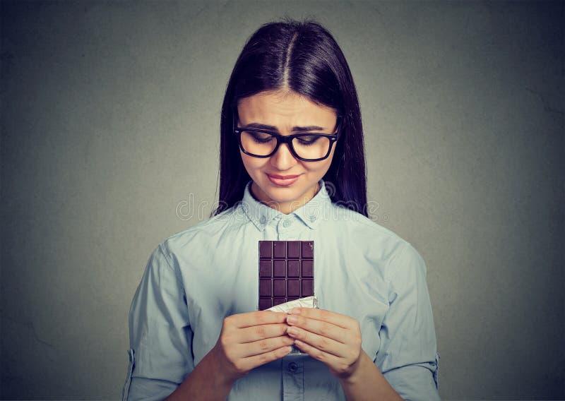 Унылая женщина утомляла ограничений диеты жаждая шоколадный батончик помадок стоковые изображения
