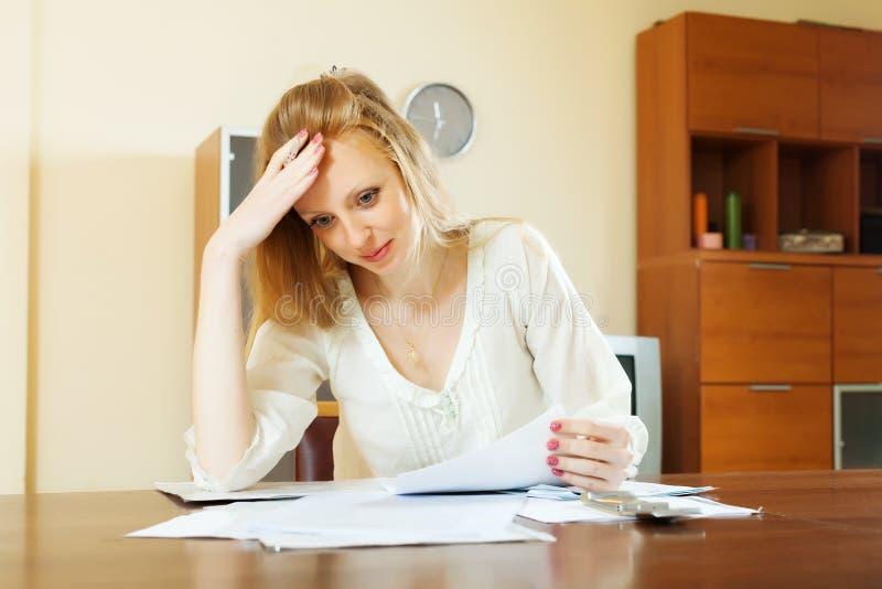 Унылая женщина читая финансовые документы стоковые фото