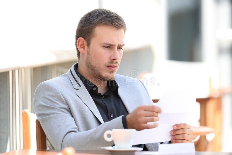 Унылая исполнительная плохая новость чтения в кофейне стоковые фотографии rf