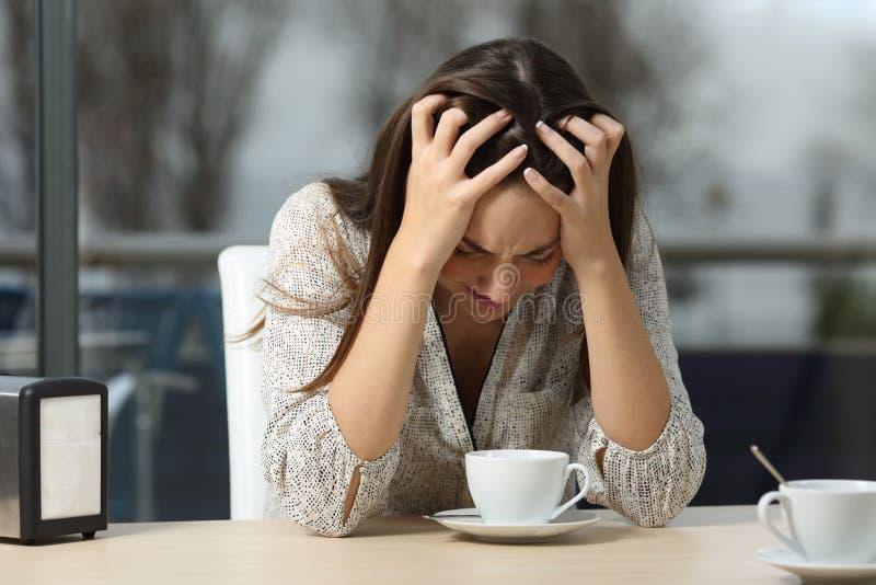 Унылая и подавленная женщина самостоятельно в кофейне стоковое фото