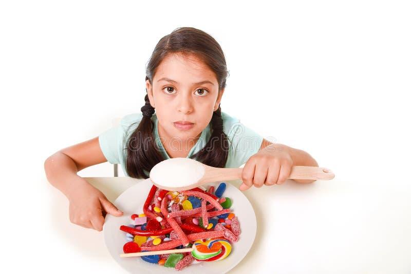 Унылая и уязвимая испанская девочка есть блюдо вполне конфеты и gummies держа ложку сахара в неправильной концепции диеты стоковое изображение rf