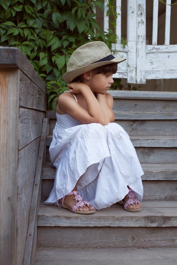 Унылая маленькая девочка сидя самостоятельно стоковое изображение rf