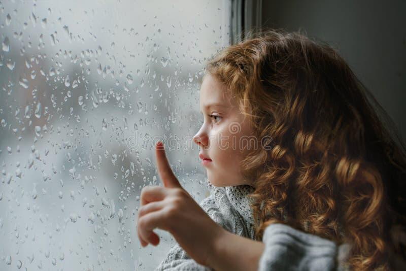 Унылая маленькая девочка смотря вне окно на дожде падает около влажного gl стоковые изображения rf