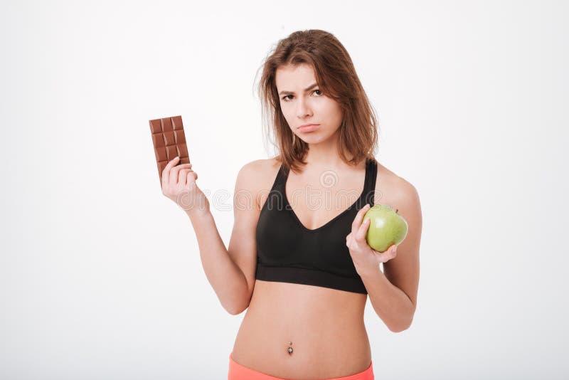 Унылая молодая дама фитнеса держа яблоко и шоколад стоковые изображения rf
