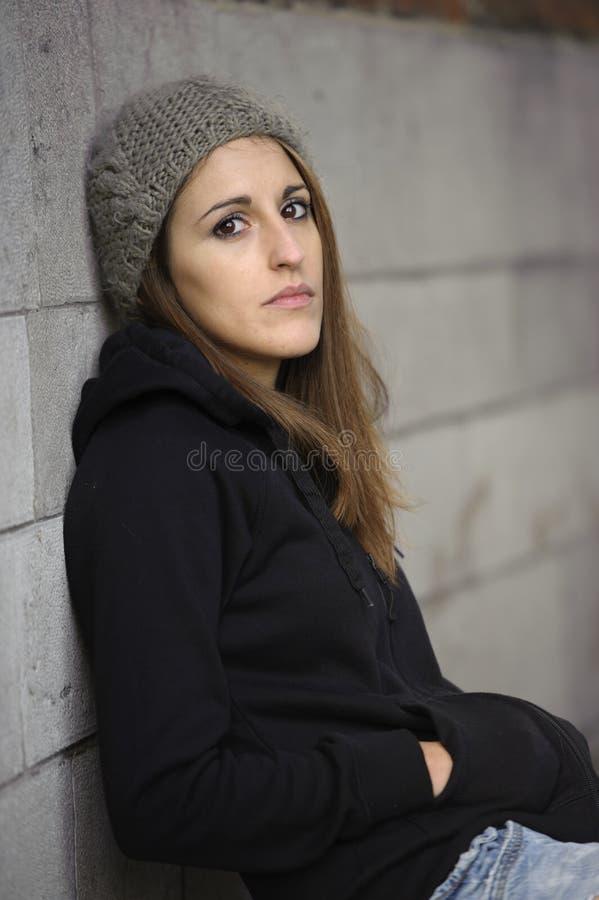 Унылая молодая женщина с связанной шляпой стоковые изображения