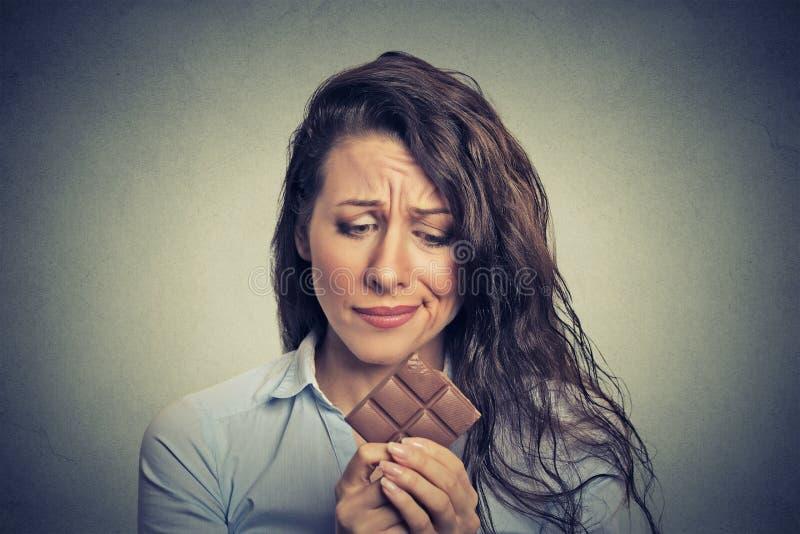 Унылая молодая женщина утомляла ограничений диеты жаждая шоколад помадок стоковые фото