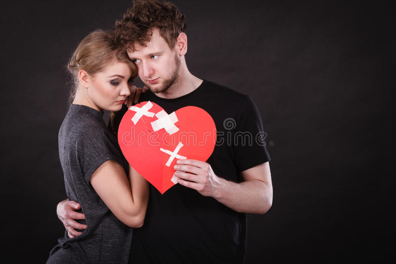 Унылая пара держит разбитый сердце стоковая фотография