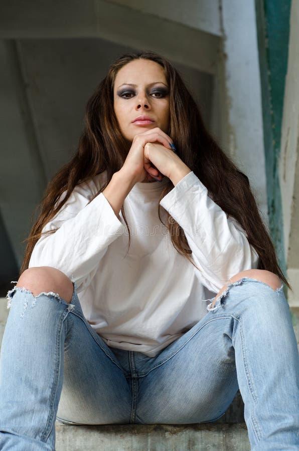 Унылая подавленная девушка сидя на лестницах покинутого здания стоковые изображения rf