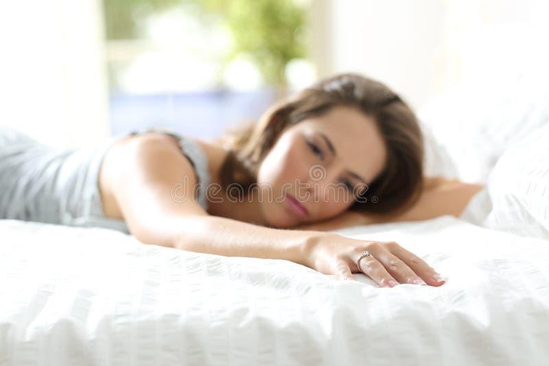 Унылая подруга скучая по ее парню на кровати стоковые фото