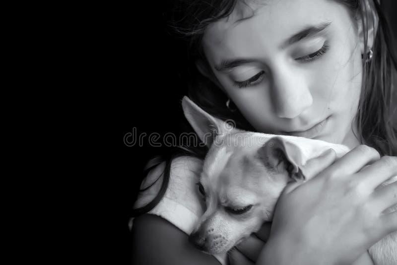 Унылая сиротливая девушка обнимая ее малую собаку стоковые изображения